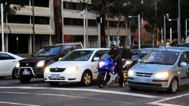 A motorcyclist waits at a red light between cars at the intersection of Northbourne Avenue and Barry Drive.