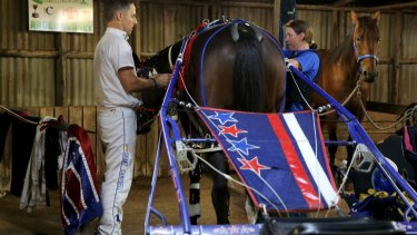 Grant Campbell assists Kerryn Manning in harnessing Arden Rooney ahead of the Terang Pacing Cup.