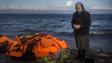 A local stands next to a pile of discarded life jackets after the arrival of refugees and migrants to the Greek island of Lesbos.