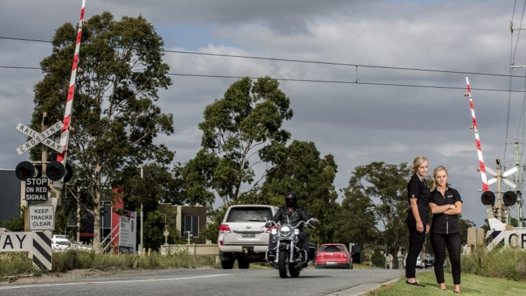 Business owners Darcie and Trish Bull at the Abbotts Road level crossing in Dandenong South.