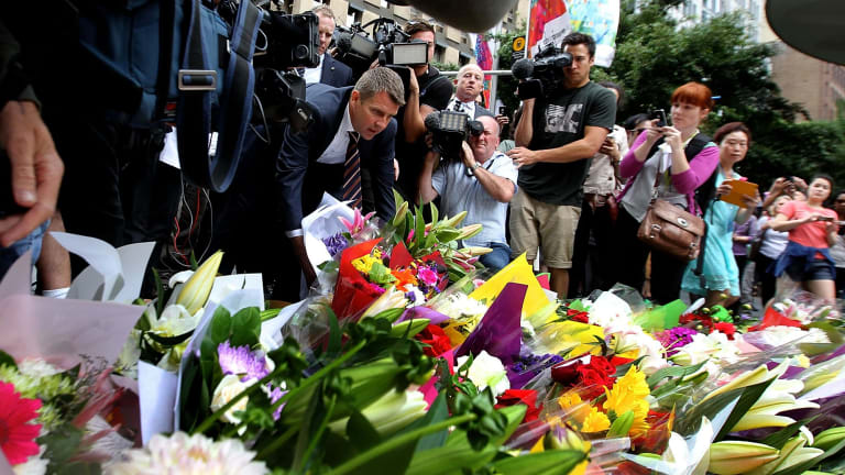 NSW Premier Mike Baird lays flowers at Martin Place after the siege.
