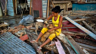 Yaneisis Martinez hugs her two dogs over the remains of her house in Isabela de Sagua, Cuba.