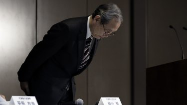 Toshiba President Satoshi Tsunakawa bows as he arrives for the news conference to announce the latest setback.