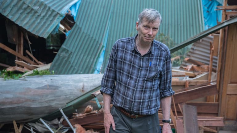 Jack Rhynsburger standing in front of the gum tree that crushed his rented home.