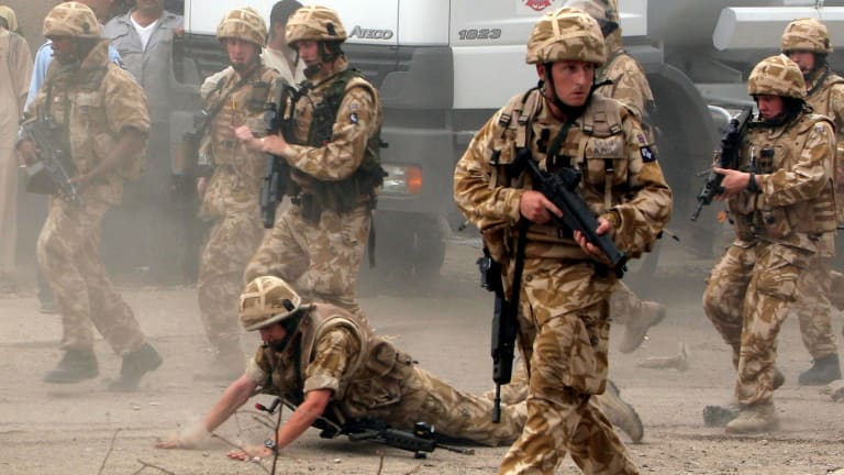 A British trooper falls after being hit by a rock in Basra in 2006.