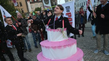 Satirical counter-demonstrators, including one dressed as Adolf Hitler and wearing a cake, pretend to celebrate the first anniversary of the first Pegida march.