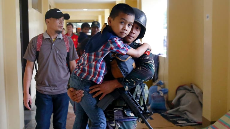 A government solider carries a boy after he was rescued from the site of the fighting between the Philippine troops and Muslim militants in Marawi city on Wednesday.