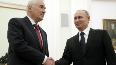 Russian President Vladimir Putin and South Ossetia leader Leonid Tibilov shake hands in Moscow.