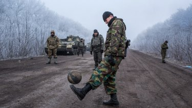 Ukrainian soldiers play football on the road leading to the embattled town of Debaltseve. The Ukrainian forces say they have been shelled regularly by Russian troops in Russia.