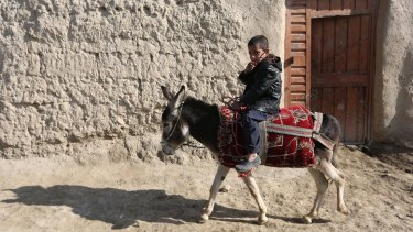An Afghan boy rides a donkey on the outskirts of Kabul on Sunday.
