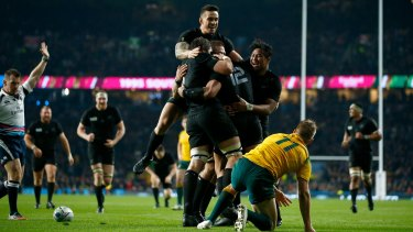 Celebration: Sonny Bill Williams jumps on the huddle after Ma'a Nonu scores New Zealand's second try.