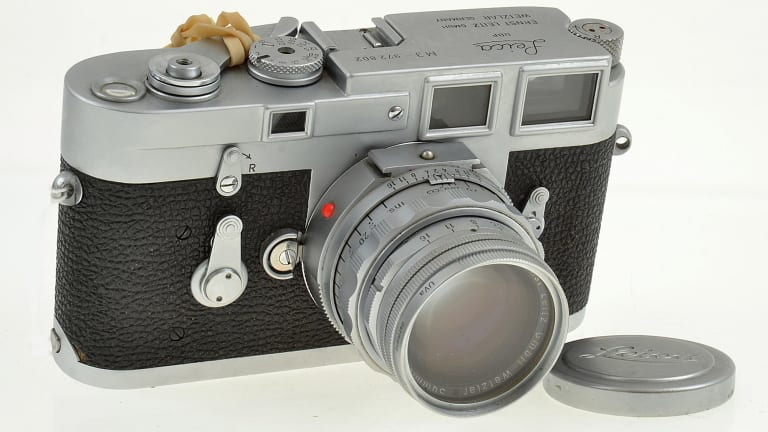 A Leica M3 (1959) with Summicron lens (1958), lens cap, UV filter and ER case. Estimates $1200 to $1600.