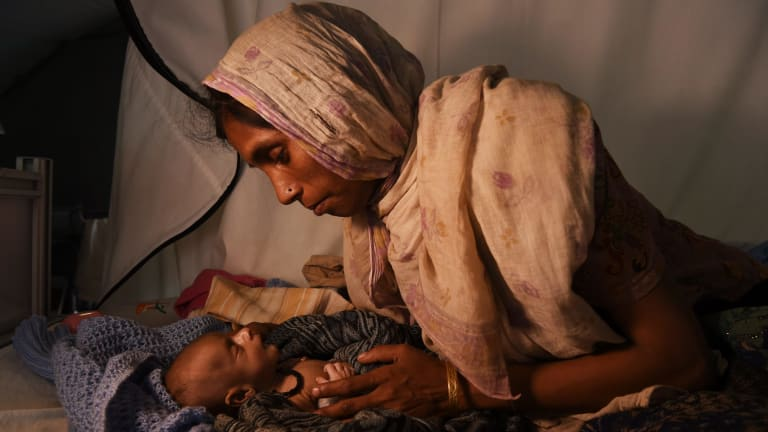 Rohingya woman Laila Begum holds her son Mohammed Ifran's hand as he receives treatment at the Red Cross Field Hospital in Kutupalong refugee camp.