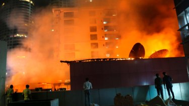 People watch as a huge fire engulfs a rooftop restaurant in Mumbai, India.