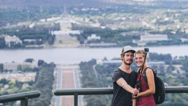 Tourists George Wootten and Hannah Barrington take a selfie with the view from Mt Ainslie