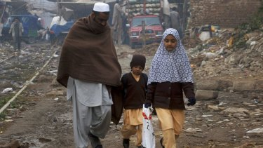 A Pakistani man walks his children home from school in the north-western city of Peshawar on Saturday.