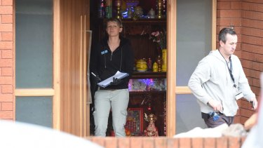 Police search a house, which appears to have a Buddhist shrine inside the front door, in Cabramatta.