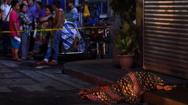 One of two people killed in a double shooting in the Manila suburb of Baclaran is left lying in the street.