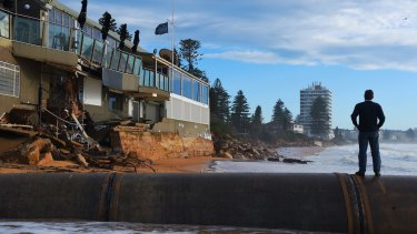 A Collaroy local surveys the damage to The Collaroy Beach Hotel on Tuesday.