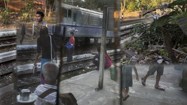 People arrive at the Phaya Lan train station in downtown Yangon, Myanmar.
