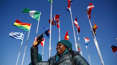 Simidele Adeagbo of the Nigerian Olympic Team snaps a photo before participating in a welcome ceremony inside the PyeongChang Olympic Village.