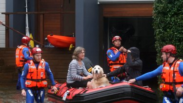 Residents evacuate their homes on Sunday as rising waters inundate Narrabeen Street in Narrabeen.