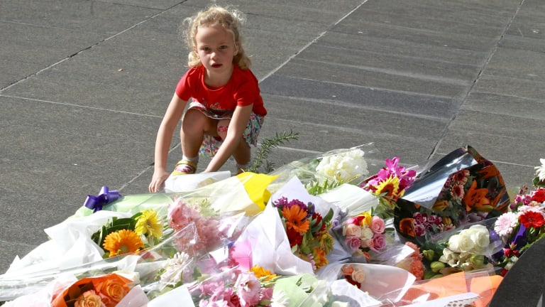 A child lays flowers for the hostages killed in the siege in Martin Place that ended early Tuesday morning.