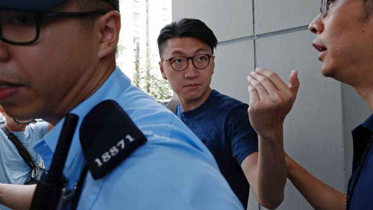 Edward Leung reacts to a group of pro-China supporters outside the court.