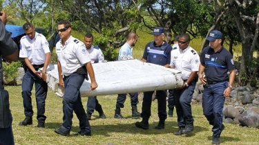 French police officers carry the flaperon which washed up on Reunion Island in July last year. It was later confirmed to be from the missing plane.