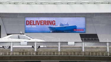 An advertising poster featuring a warship at Canberra Airport.