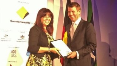 Eman Sharobeem receives her commendation in the Australian of the Year Award from then-NSW premier Mike Baird.