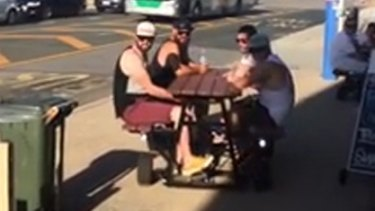 The men were all smiles as they drove passed confused patrons at a cafe, one offering a thumbs-up.