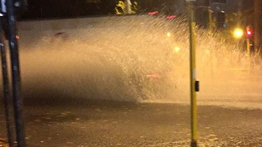 A car splashes through a puddle in East Perth.