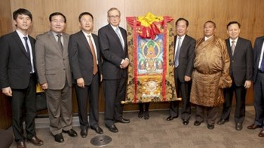 """Bob Carr with Zhu Weiqun (also standing next to the scroll) and """"living buddha"""" Tudeng Kezhu (in robe) in a photo which appeared in the People's Daily, the Communist Party's flagship newspaper."""