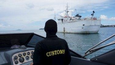 Customs officials approach the 'Taisan'.