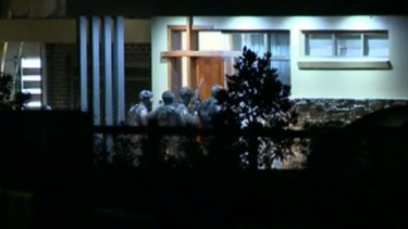 Tactical Operations Unit officers enter a home in Luddenham about midnight.