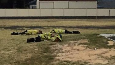 Exhausted firefighters kip on the lawn outside Harvey fire station during the Yarloop bushfire disaster.