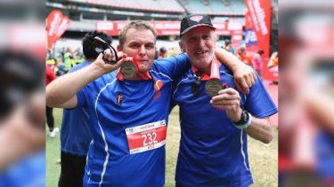 Homeless runners Kyle Holtzman and Ian Brown Brown display their medals after completed the Melbourne Marathon.