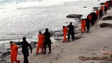 A screenshot from the video shows men being led along the beach.