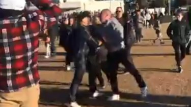 Spectators fighting after an umpire was chased from the ground at a junior football game.