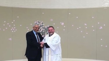 The Grand Mufti, Dr Ibrahim Abu Mohamed, is pictured in the Islamic State video shaking hands with inter-faith advocate and Anglican minister Father Rod Bowers.