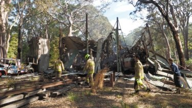 NSW Fire and Rescue officers sort through the remains of the destroyed storage shed at the Sydney Tramway Museum.