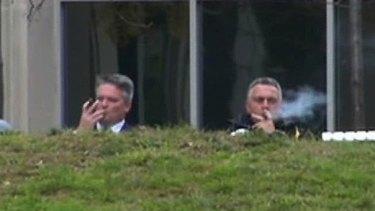 Finance Minister Mathias Cormann and Treasurer Joe Hockey enjoy cigars outside The Treasury in Canberra.