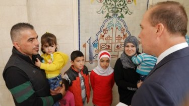 Immigration Minister Peter Dutton hands a refugee visa to the Syrian refugee family of Marwan Alkhdah in Jordan earlier this month.