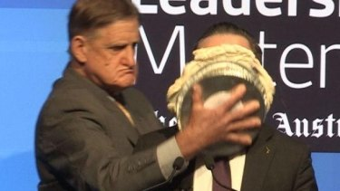 Alan Joyce hit with a pie during an event in Perth on Tuesday.