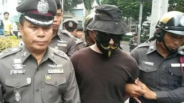 A man in a Guy Fawkes mask and sunglasses is escorted by Thai police in Bangkok.