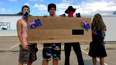 Men stood on top of a Townsville shopping centre holding a racist sign in the wake of the Sydney siege.
