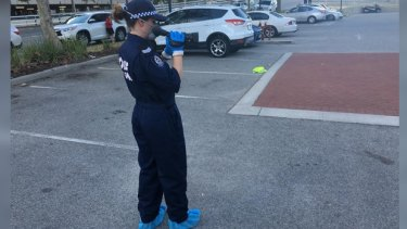 Police examine the site outside Officeworks in East Perth, where the man was Tasered.