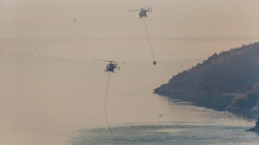 Helicopters fill monsoon buckets from Lyttelton Harbour, south of Christchurch.