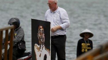 Lawyer Julian McMahon carries a self-portrait painted by Myuran Sukumaran, after visiting the prison island of Nusakambangan.